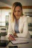 Femme lisant et signant le contrat au bureau S Photo stock