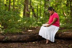 Femme lisant la bible dans Forest Preserve While Sitting sur un rondin photo stock