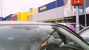 Femme lisant le catalogue d'IKEA à l'intérieur du stationnement de voiture banque de vidéos