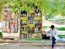 Femme lisant le papier par une bibliothèque de prêt en parc à Santiago, Chili Photos stock