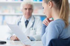 Femme lisant les disques médicaux Images stock