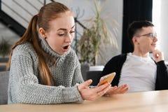 Femme lisant ses messages de fraude du ` s d'homme sur le sien téléphone image stock