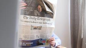 Femme lisant Daily Telegraph banque de vidéos