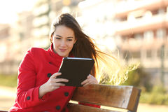 Femme lisant un ebook ou un comprimé en parc urbain Photos stock