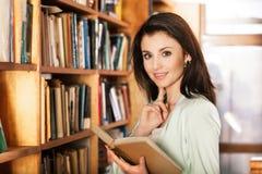 Femme lisant un livre devant des étagères Photographie stock libre de droits