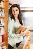 Femme lisant un livre devant des étagères photos libres de droits