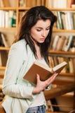 Femme lisant un livre devant des étagères photo libre de droits