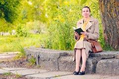 Femme lisant un livre en parc au printemps Photographie stock