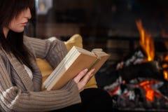 Femme lisant un livre par la cheminée image stock