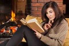Femme lisant un livre par la cheminée photos stock