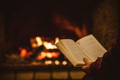 Femme lisant un livre par la cheminée Jeune femme affichant un livre photographie stock