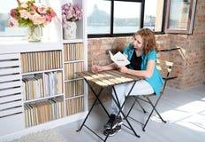 Femme lisant un livre sur la chaise près de la fenêtre Image stock