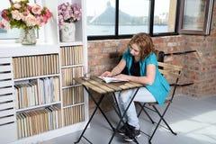 Femme lisant un livre sur la chaise près de la fenêtre Photos libres de droits
