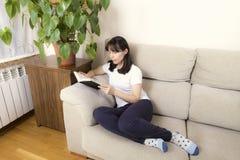 Femme lisant un livre sur un sofa Image stock