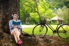 Femme lisant un livre tandis que musique de écoute photographie stock libre de droits