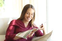 Femme lisant un magazine à la maison Photo stock