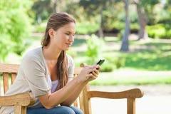 Femme lisant un message textuel sur un banc de parc Image stock