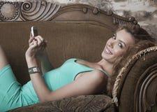 Femme liying sur le sofa Photographie stock
