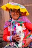 Femme locale dans la robe traditionnelle tenant l'agneau dans la rue de C Image libre de droits