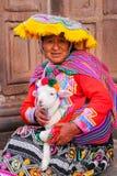 Femme locale dans la robe traditionnelle tenant l'agneau dans la rue de C Image stock