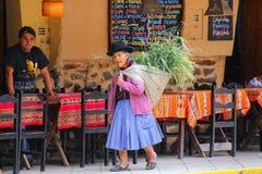 Femme locale marchant avec le keperina plein de l'herbe dans la rue de Images stock