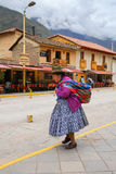 Femme locale marchant dans la rue d'Ollantaytambo, Pérou Photographie stock libre de droits