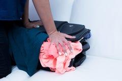 Femme luttant pour emballer la valise Photo stock