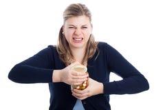 Femme luttant pour ouvrir la bouteille Image libre de droits