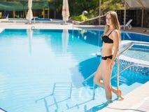 Femme luxueuse marchant à la piscine sur un fond de station de vacances Concept de station estivale Copiez l'espace Photos stock