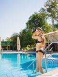 Femme luxueuse marchant à la piscine sur un fond de station de vacances Concept de station estivale Copiez l'espace Photographie stock libre de droits