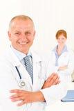 Femme mâle de sourire aînée d'équipe médicale jeune Image stock