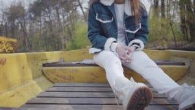 Femme méconnaissable de charme dans le pantalon blanc et des chaussures se reposant dans le vieux bateau jaune sur la rivière Le  banque de vidéos