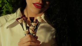Femme méconnaissable tenant les fleurs artificielles banque de vidéos