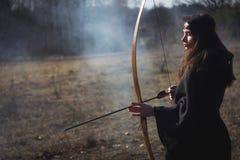 Femme médiévale de guerrier avec l'arc dans le champ de bataille photos stock