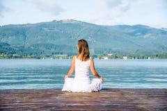 Femme méditant au lac photos libres de droits