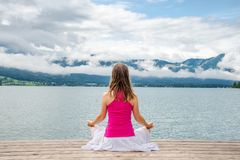 Femme méditant au lac image libre de droits