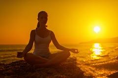 Femme méditant dans la pose de lotus au coucher du soleil image stock