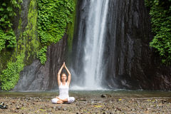 Femme méditant faisant le yoga entre les cascades Images stock