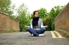 Femme méditant sur la passerelle Photographie stock libre de droits