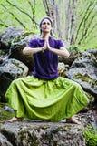 Femme méditant sur la roche photos stock