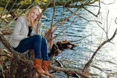 Femme mélancolique blonde s'asseyant par un lac Image stock