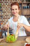 Femme mélangeant la salade de légume frais Photos stock