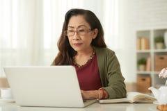 Femme mûr avec l'ordinateur portatif Photographie stock libre de droits