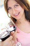 Femme mûr grillant avec le vin rouge Image stock