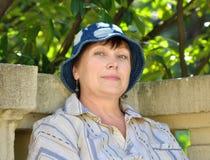 Femme mûr s'asseyant sur un banc de stationnement Image libre de droits