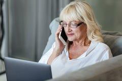 Femme mûre à l'aide de l'ordinateur portable Image stock