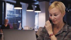 Femme mûre à l'aide de l'ordinateur portable et faisant la conversation sur le telep futé clips vidéos