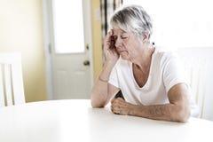 Femme mûre à la maison touchant sa tête avec ses mains tout en ayant une douleur de mal de tête Photo stock