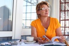 Femme mûre à la table avec le livre et la cuvette en matin Images stock