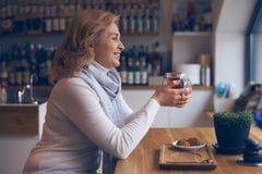 Femme mûre affectueuse s'asseyant en café avec la tasse de thé Image stock